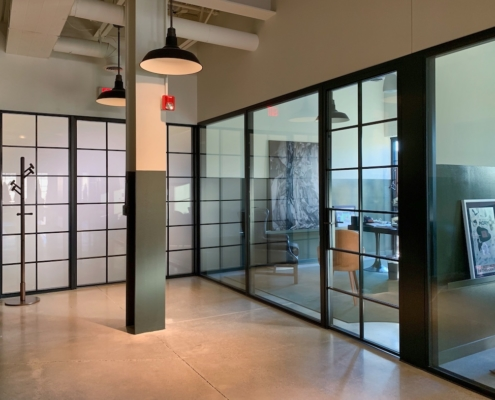 window wall, fixed window, single hinged doors, muntin grids, obscured glass