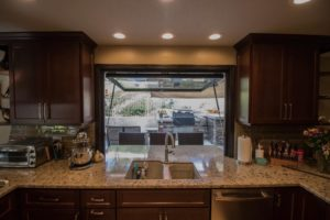 kitchen sink pass through window opening up to an outdoor patio